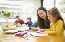 Мати і дочка, робити домашнє завдання в обідній стіл — стокове фото