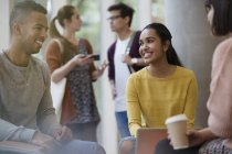 Smiling college students studying drinking coffee — Stock Photo