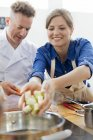 Woman placing food in pot in cooking class kitchen — Stock Photo