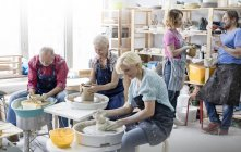 Mature students using pottery wheels in studio — Stock Photo