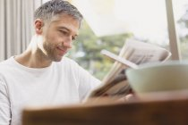 Man reading newspaper at breakfast — Stock Photo