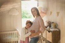 Porträt lächelnde schwangere Mutter und Tochter im Kinderzimmer — Stockfoto
