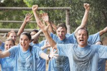 Enthusiastic team cheering in rain on boot camp obstacle course — Stock Photo