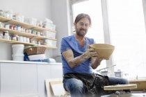 Портрет уверенный в себе зрелый мужчина держит чашу на гончарном круге в студии — стоковое фото