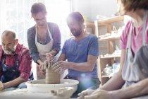 Керівні зрілою людиною на гончарному колі у студії вчителя — стокове фото