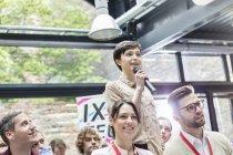 Женщина с микрофоном задает вопрос аудитории на конференции — стоковое фото