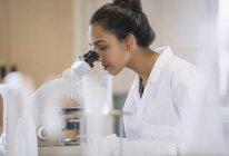 Female scientist using microscope in laboratory — Stock Photo