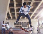 Friends watching teenage boy flipping skateboard at skate park — Stock Photo