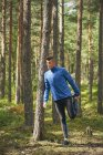 Runner stretching leg at tree in woods — Stock Photo