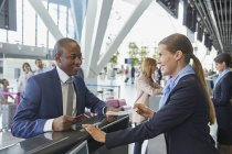 Uomo d'affari aiutando rappresentante di servizio clienti al banco check-in aeroporto — Foto stock
