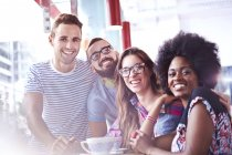 Portrait of smiling friends in modern cafe — Stockfoto