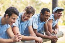Equipe sorrindo apoiando-se em trilhos no acampamento de inicialização — Fotografia de Stock