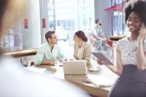 Business people talking face to face in cafe — Stock Photo