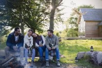 Friends drinking beer relaxing at campfire outside cabin — Stock Photo