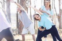 Instructora de yoga guiando a una mujer mayor en el parque - foto de stock