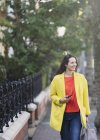 Smiling woman walking with cell phone in urban park — Stock Photo