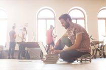 Випадковий бізнесмен, що працюють на ноутбук з скейтборд — стокове фото