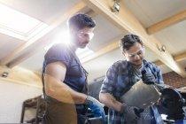Metal workers using sander in workshop — Stock Photo