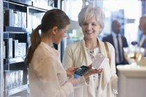 Femme achetant parfum dans la boutique de commis avec lecteur de carte de crédit sans fil — Photo de stock