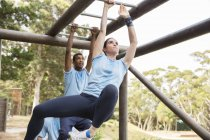 Determined woman swinging on monkey bars on boot camp obstacle course — Stock Photo
