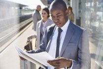 Businessman reading paperwork on sunny train station platform — Stock Photo