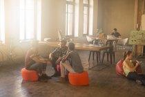 Personas de negocios informal reunión en círculo en oficina soleada - foto de stock