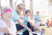 Mulher sênior Orientador de ioga instrutor no parque ensolarado — Fotografia de Stock