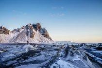 Женщина, стоя среди отдаленных, ледяной пейзаж, Höfn, Исландия — стоковое фото