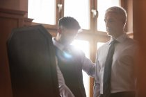 Tailor fitting businessman at mirror in menswear shop — Stock Photo