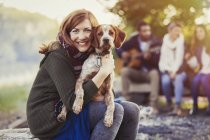 Portrait smiling woman hugging dog at campsite with friends — Stock Photo