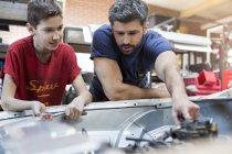 Отец и сын чинят автомобильный двигатель — стоковое фото