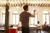 Empresario informal revisar diagramas de colgar en la oficina - foto de stock