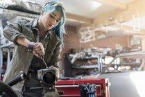 Молода жінка механіка з синє волосся відновлення участь в авто ремонт магазин — стокове фото
