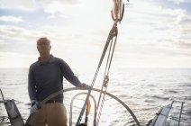 Retired man sailing steering sailboat at helm — Stock Photo