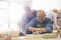Senior couple molding clay in pottery studio — Stock Photo