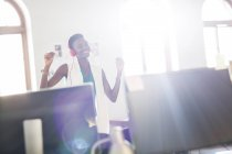 Enthusiastic businesswoman wearing headphones and dancing in office — Stock Photo