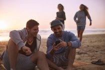 Amigos sair mandando mensagens com o celular na praia do sol — Fotografia de Stock