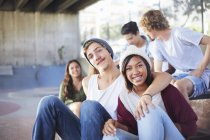 Portrait smiling teenage couple hanging out with friends at skate park — Stock Photo