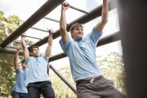 Determined men crossing monkey bars on boot camp obstacle course — Stock Photo