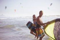 Portrait couple souriant avec matériel de kitesurf en surf océanique — Photo de stock