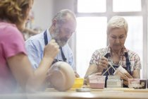 Senior couple painting pottery in studio — Stock Photo