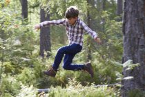 Energetic boy jumping in woods — Stock Photo
