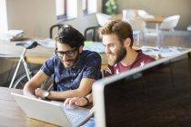 Casual hommes d'affaires travaillant à l'ordinateur portable au bureau — Photo de stock