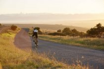 Male triathlete cyclist cycling on sunny rural road at sunrise — Stock Photo
