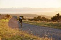Велосипедист мужской пловца, Велоспорт на Солнечный сельской дороге на рассвете — стоковое фото