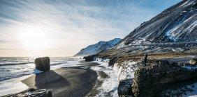 Сонце світить над крижаний пляж і гори, Ісландія — стокове фото