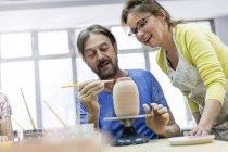 Зрелая пара рисует керамику в студии — стоковое фото