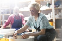 Mature woman using pottery wheel in studio — Stock Photo