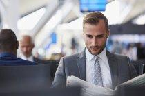 Uomo d'affari, leggere il giornale in zona partenza aeroporto — Foto stock