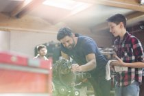 Father and son rebuilding car engine in auto repair shop — Stock Photo